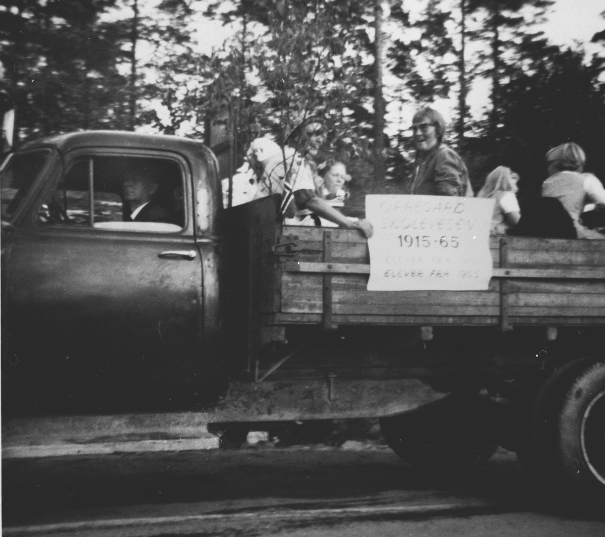 Opptog i forbindelse med Oppegård kommunes 50-års jubileum. Deltakere på et lasteplan.