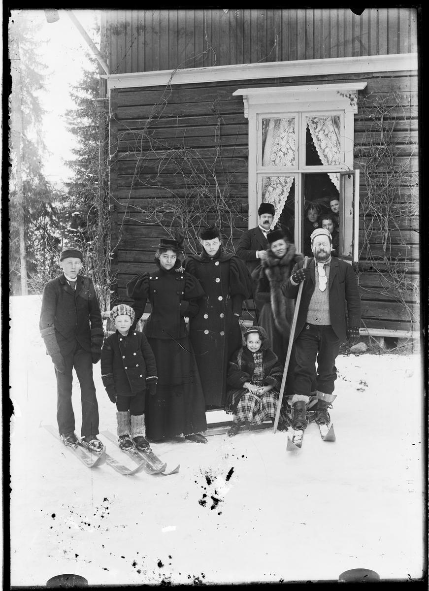 Mannge mennesker oppstilt foran hus med kjelke og ski.