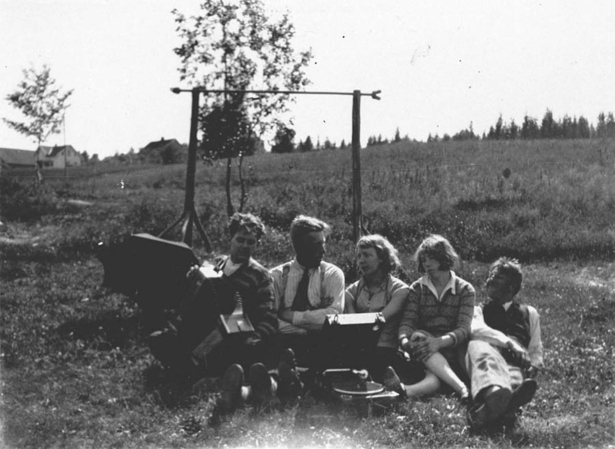 Unge mennesker som spiller grammofon, paraply, høydehoppstativ.