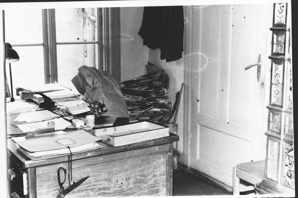 Det gamle politikammeret i Lillestrøm. Kontor skrivebord dekket med papirer. I bakgrunnen er uryddig haug med bilskilt.