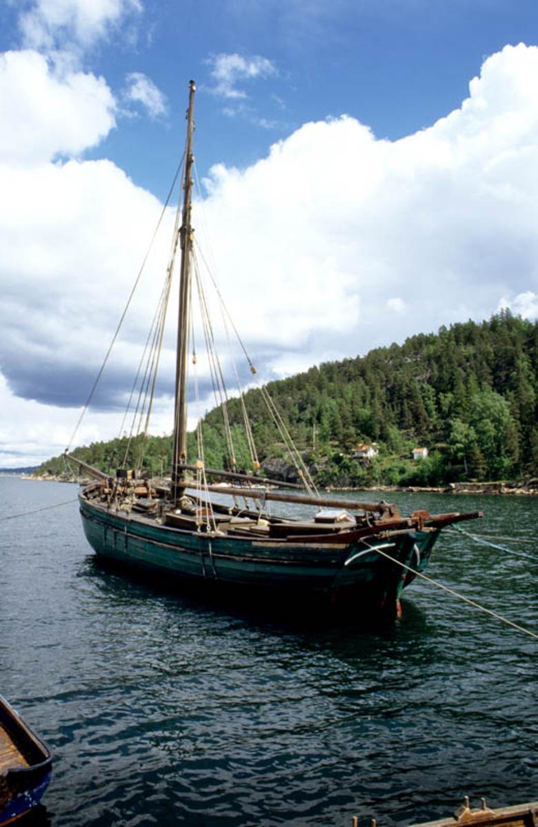 Oslofjorden. Fortøyd veteranbåt, treskute med en mast.
