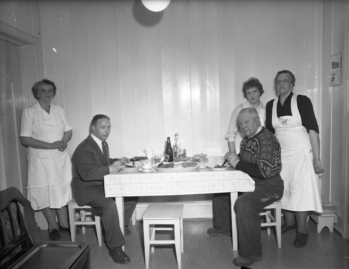 2 menn spiser – 3 kvinner serverer. Øl og akevitt på bordet.