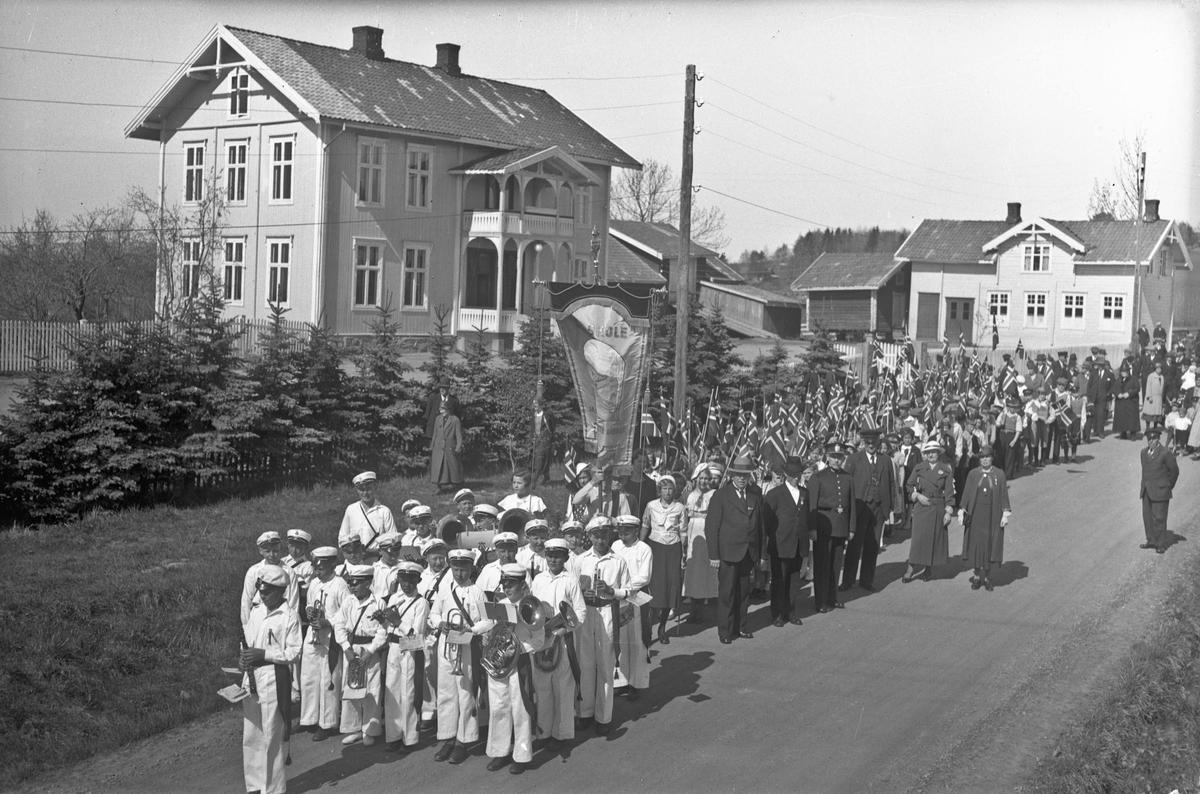 Korps i tog. Fane fra Ås skole. Lensmann Johan Aasgaard (f. 1881, og var lensmann fram til 1945) i uniform. Fra 1920-30-tallet. Gamle Ås skole til venstre. Den lå omtrent der skolen ligger i dag.