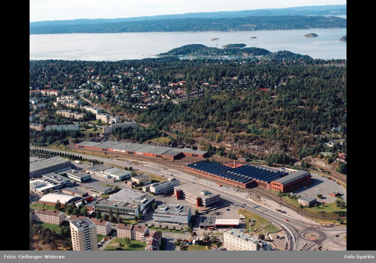 Europaveien (E 6), Ryensvingen. Ryenkrysset. Lambertseterbanen. Ryen industriområde. Vognhall / verksted for T-banen. Bekkelagshøgda i bakgrunnen. Ormøya, Malmøya og fjorden bakerst. (Flyfoto)