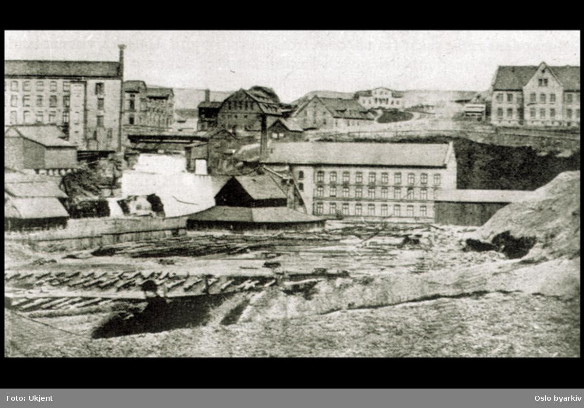 Fotografiet er en avfotografering fra en bok, og viser fossen ved Sagene. Hjula veveri til venstre. Akerselva.