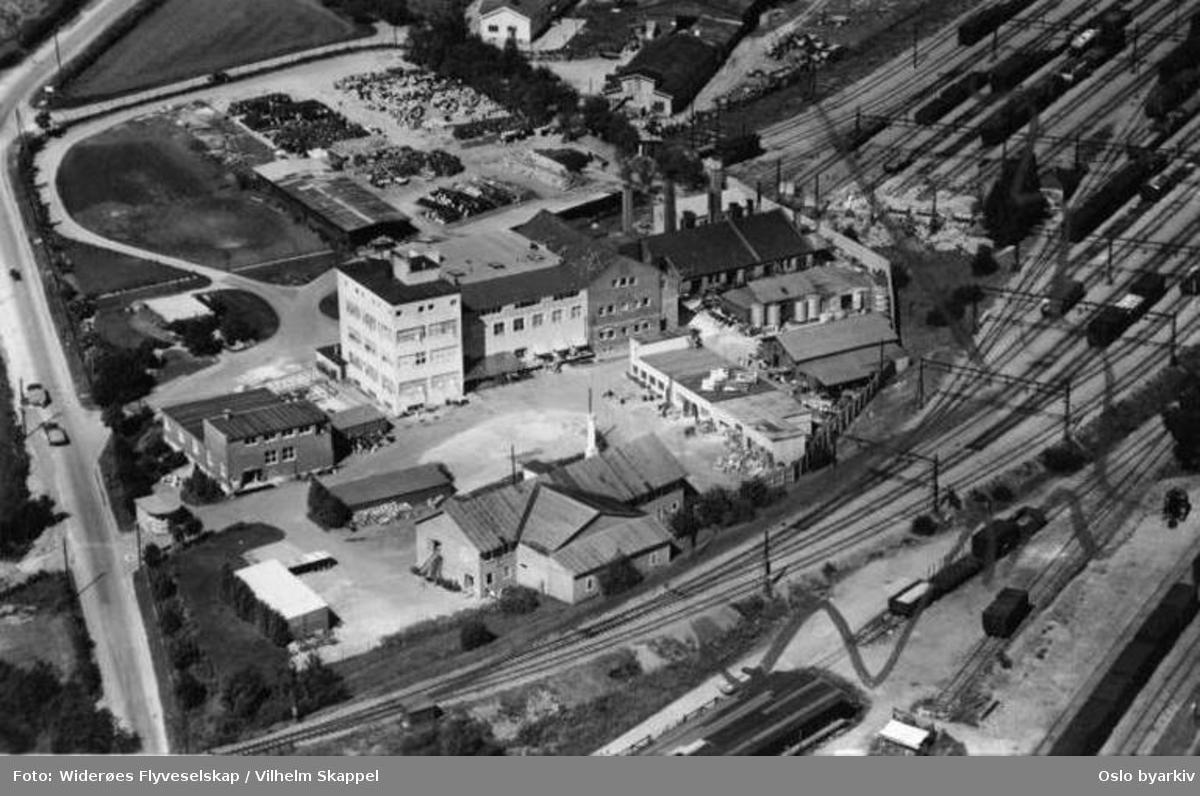 Fabrikkbygning, malingsfabrikk, Hovedbanen, tog, lagring av tønner (Flyfoto)