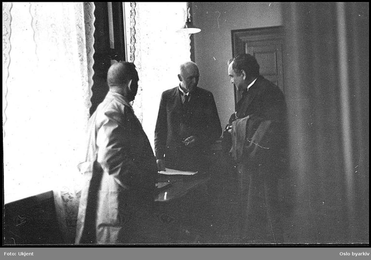"""Tre lærere i diskusjon på overlærerens kontor. Albumtittel: """"Sofienberg skole femti år - første september 1933."""""""