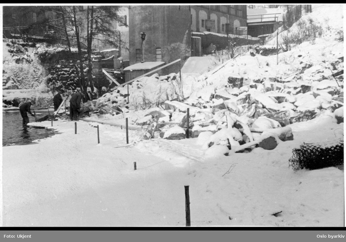 Vinter ved Akerselva nedenfor Øvre Vøyen foss. Glads mølle (Nedre Papirmølle), med turbinhuset i front, midt i bildet. Hjula Væveri (Veveri) oppe i venstre hjørnet. Arbeidere i gang med forbredelse til steinlegging av elvas østre elvebredd.