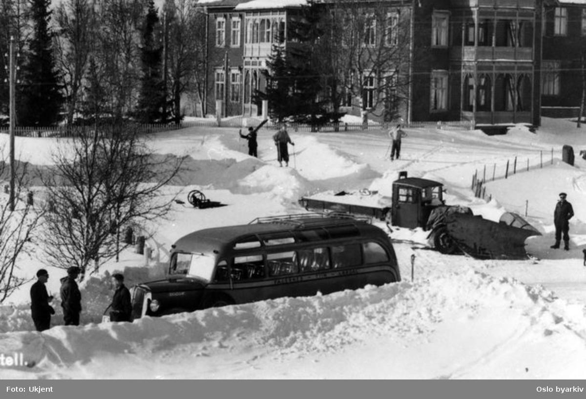 Vinterbilde fra ukjent sted, rutebuss merket Fagernes - Lærdal, snømåkerbil, folk på ski, hotell bak. Sannsynligvis fra Fagernes, og utsnitt fra et postkort, jf. del av påskrift nedre venstre hjørne.