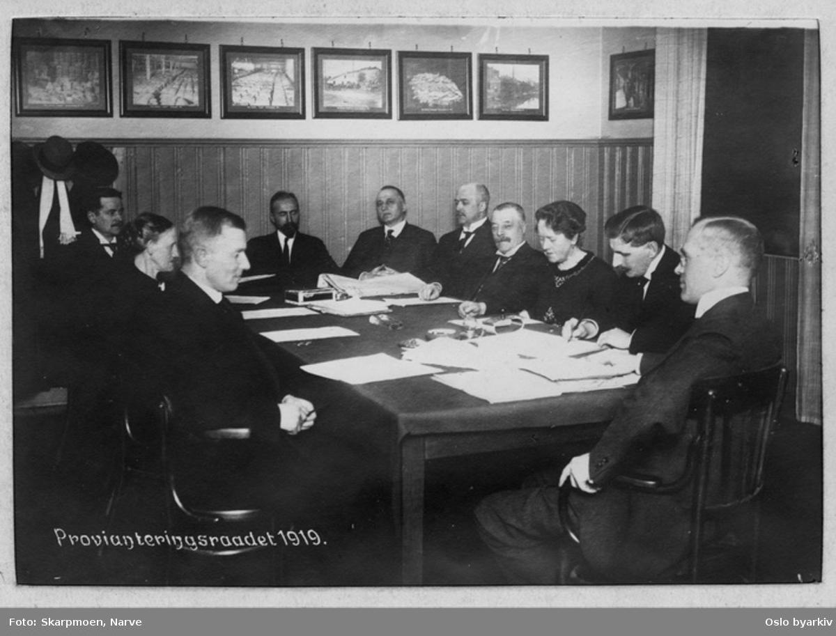 Ni menn, to kvinner - provianteringsrådet fotografert under arbeid, bilder i bakgrunnen - de samme bildene som er i dette arkivet; dkumentasjon av provianteringsrådets arbeid.
