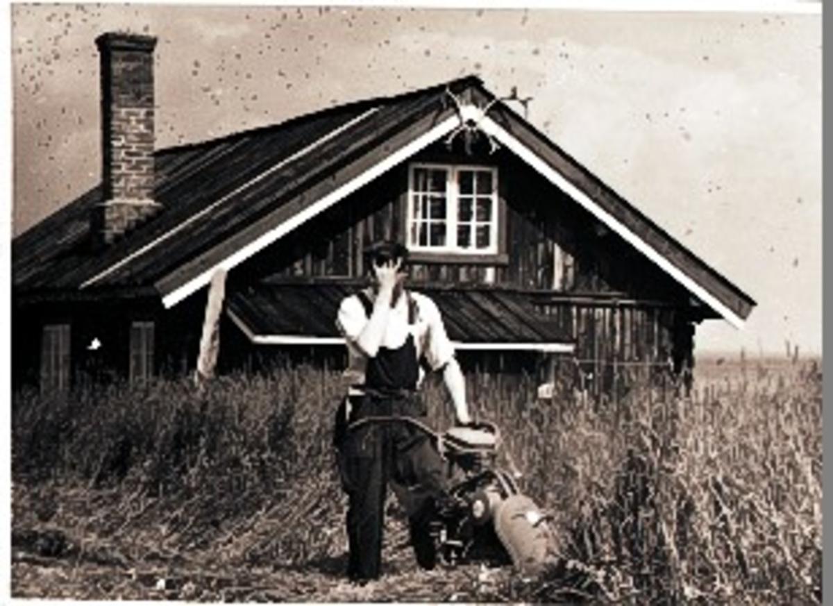 Svein Olavson Løstegård i grasslåten. Hytte, motorslåmaskin, overall og skjorte.