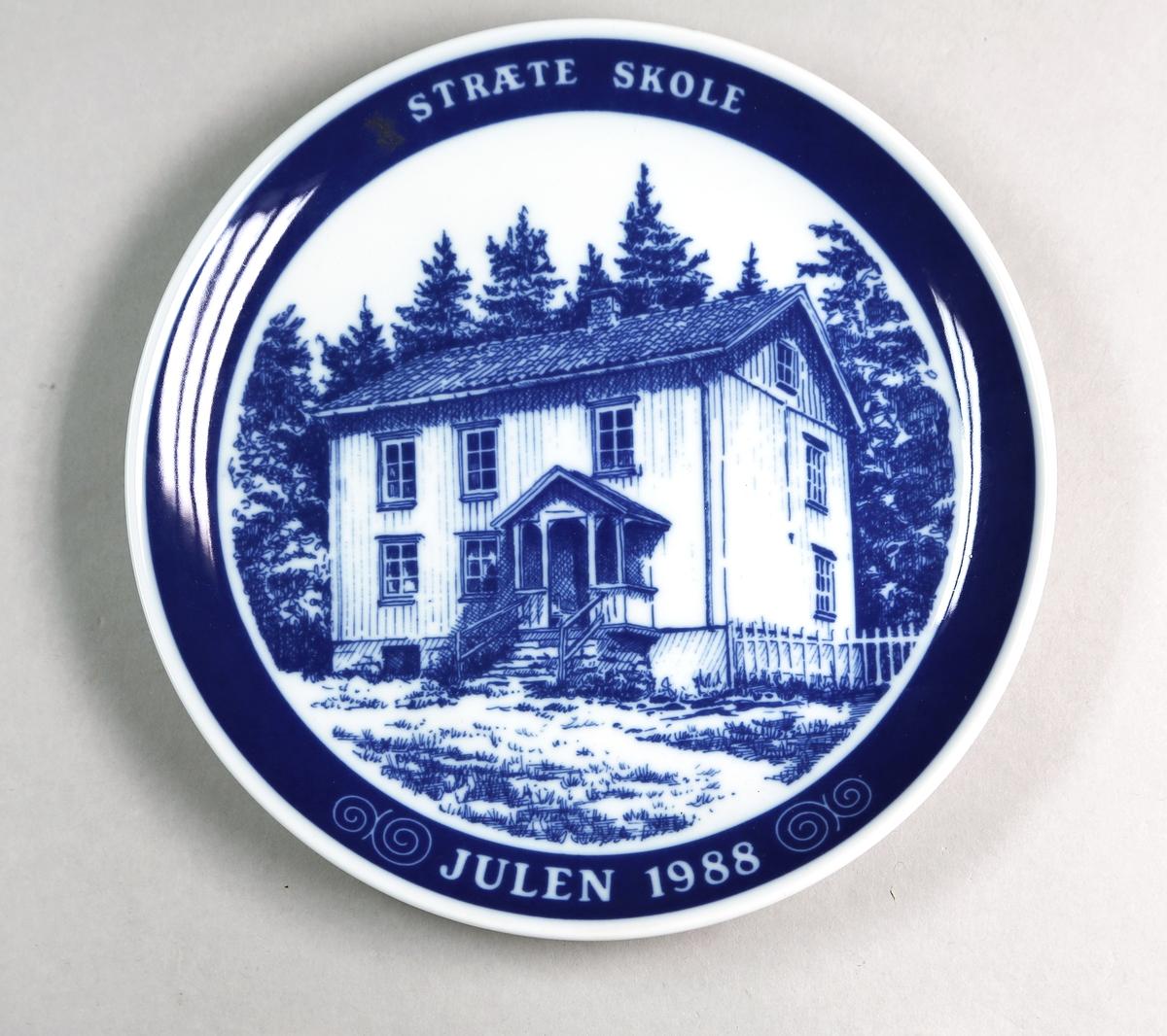 Rund tallerken med Stræte skole som dekormotiv, med en blå bord omkring med skrift.