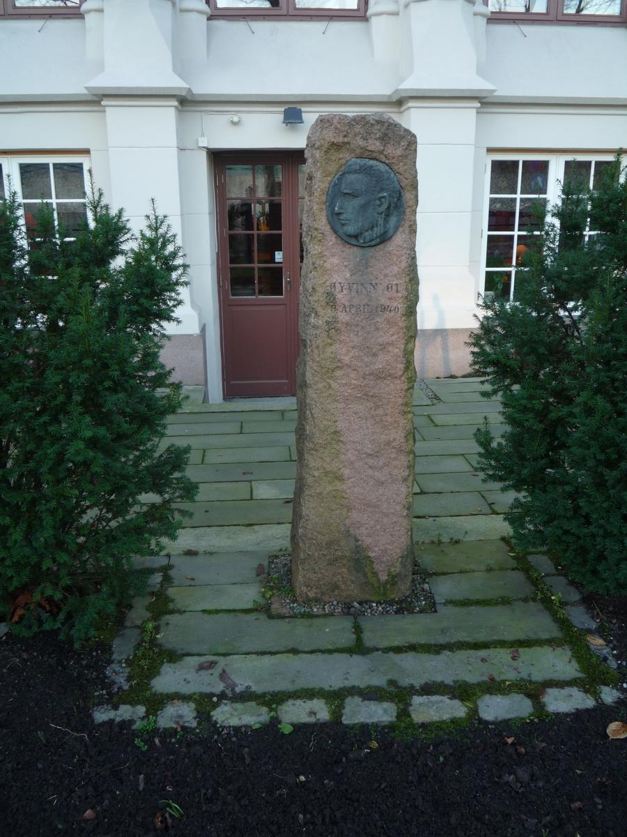 Krigsminnesmerke. Relieff, mann i profil, medaljong. Rød granitt, grovt hugget, bronserelieff.