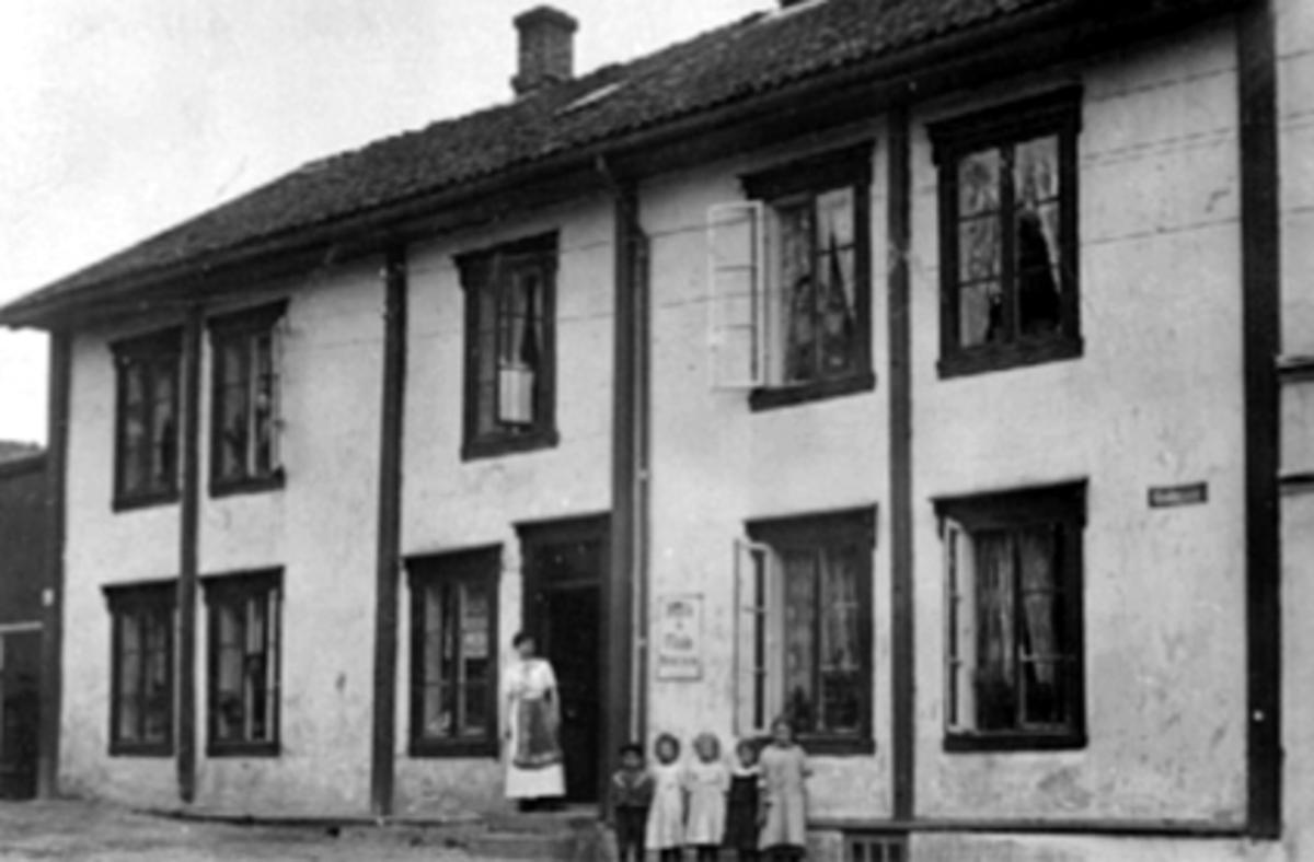 Eksteriør, Vestbyen kolonial, folk.  Foran huset fra v: Thora Rønning (f. Kirkeby), O. G. Evensen (f. 26. 9. 1906), Asbjørg Hagen (f. Nilsen 16. 6. 1905), Lucie Jølstad (f. Nilsen 26. 1. 1904), Dagmar Kartomten (f. Gundersen 29. 4. 1906), Gudrun Monsen (f. 30. 3. 1903).  Se En innlandsby vokser fram. bilde nr. 115