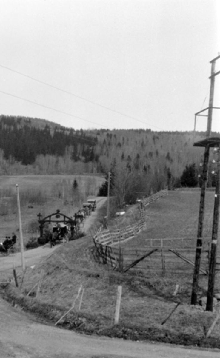 Biler i begravelsesfølge i svingen ved Mørkved store i 1926, passerer under portal av granbar. Hotelldirektør Albert Alexander Paterson F.1857-25.41926 fraktes fra Høsbjør til Brumunddal stasjon for å sendes til Bergen. Snøgrinder på jordet er ikke fjernet etter vinteren.