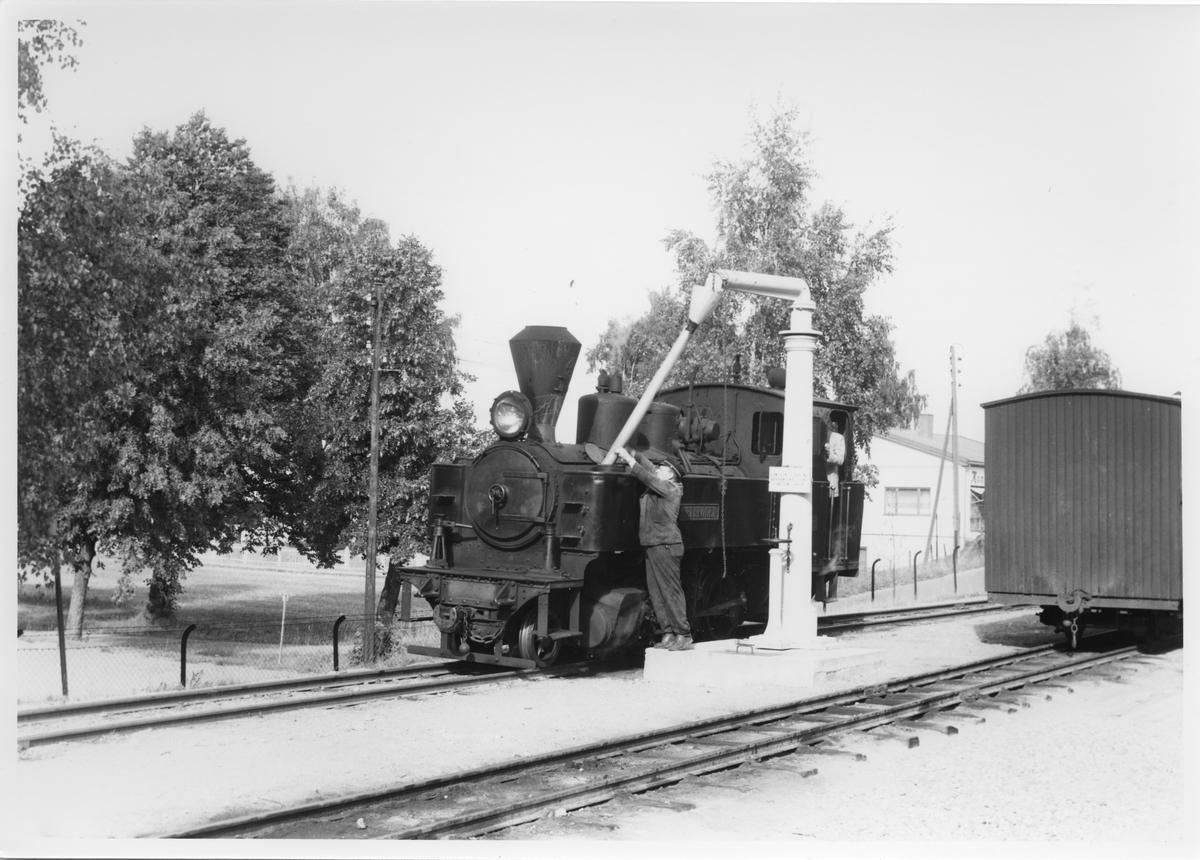 Lok 4 Setskogen tar vann på Sørumsand stasjon.  Haugers bakeri bak t.v.