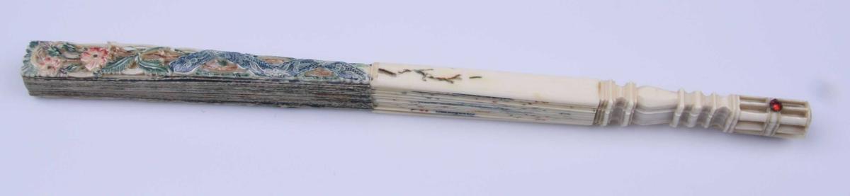 Viften er av papir med spiler av ben, balusterformet utskåret nederst og festet sammen med en stift som ender i en rubin-lignende sten på hver side. Endestykkene er dessuten øverst utskåret som blomsterranke og knekket kniplingbånd og bemalt. Den flate delen av spilene er bemalt på forsiden med polykrome blomstergrener, knekkete kniplingsbånd og hatt, kårde og stav samt fakkel og brett omgitt av båndsløyfer og satt inn i kartusj trukket opp med gull. På vifteplaten en hyrdescene på blå grunn omgitt av gullrand og malte felter av kniplinger, blomstergrener og insekter, de siste i gull. På baksiden landskap med hus omgitt av polykrom blomsterbord. Landskapet og huset har svakt kinesisk preg.