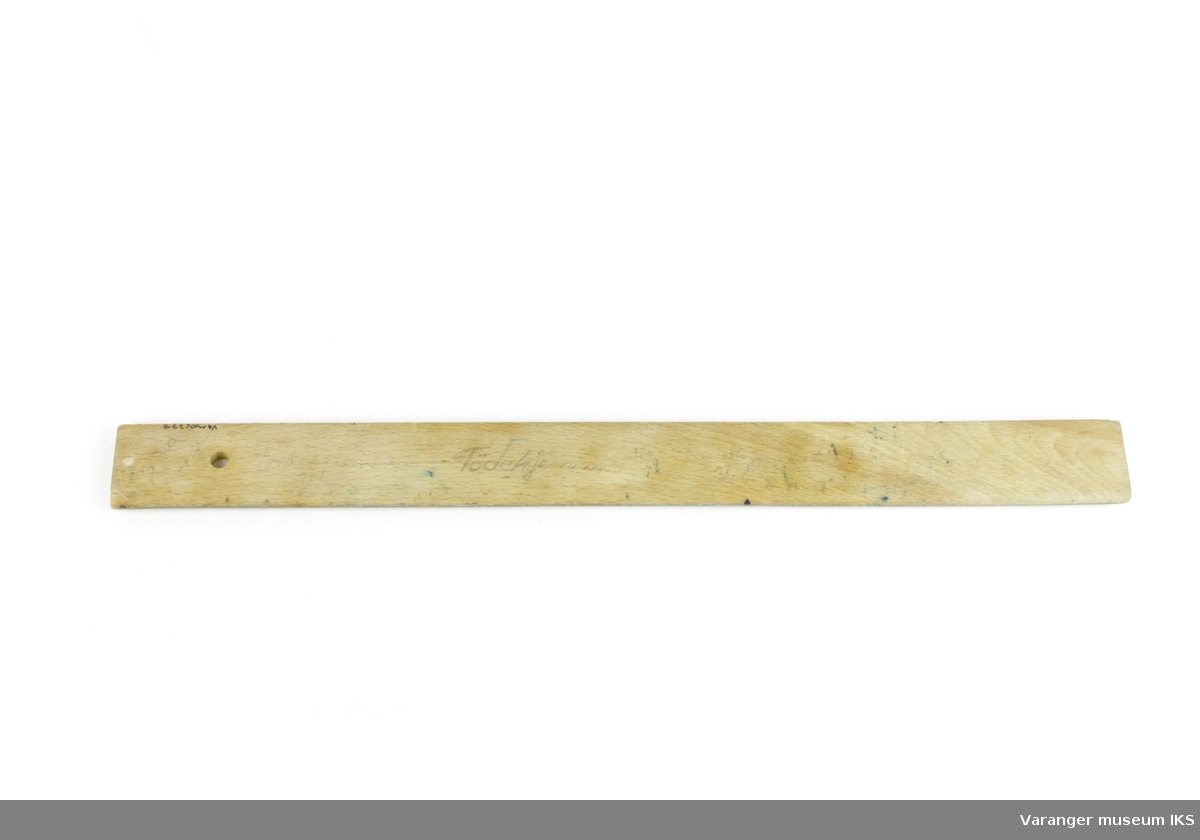 Linjal i tre. 0,5 cm tykk med hull til opphenging i venstre ende.