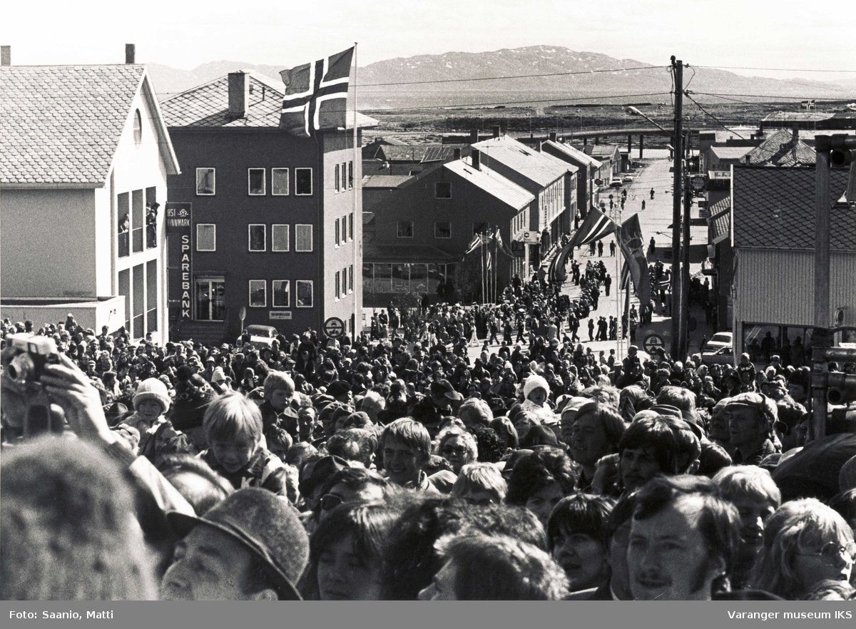 Opptog i gata under avdukingen av Innvandrermonumentet/Kvenmonumentet i Vadsø. Folkmengden ned mot Tollbugt. og mot Vadsøya 1977.