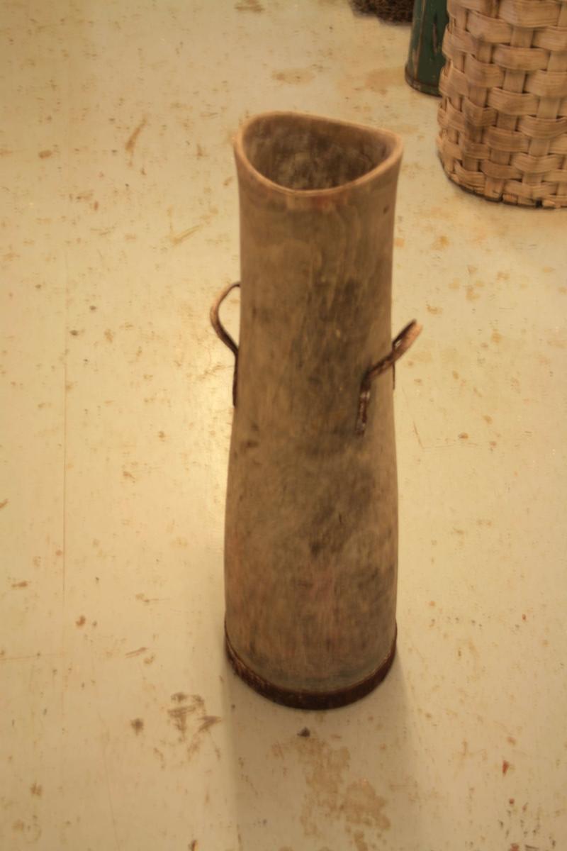 Sylinderforma gjenstand. Gjenstanden er utforma i eit trestykke. Omlag midt på gjenstanden er det fest handtak i hampetau.