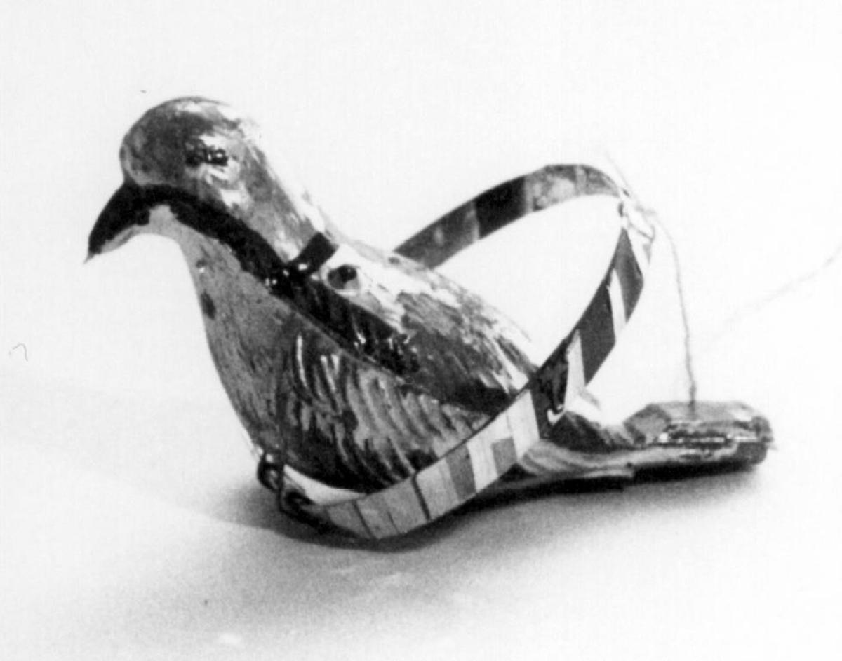 Spaltefløyte. Barneleke i form av plastfugl med spalte og blåsekant i stjerten. Fuglen er utvendig dekorert med sølvfarget og rød maling og sitter på en papirbelagt plastring.