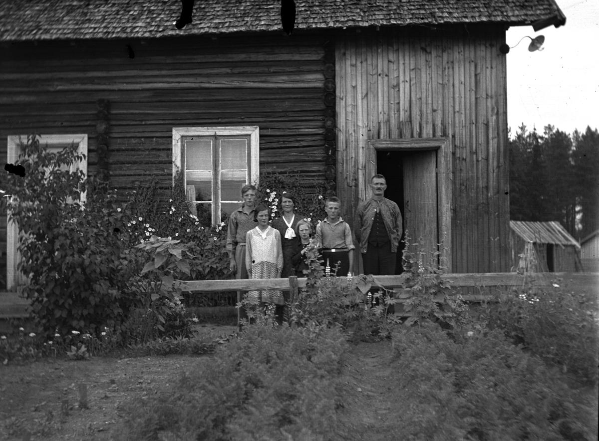 Ukjent familie står foran et hus.