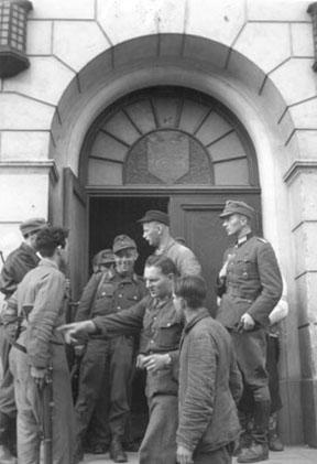 FREDSDAGENE I HAMAR, MAI 1945, NORSKE HJEMMEFRONTSOLDATER INNTAR FRIMURERLOSJEN I ØSTREGATE 54.  På bilde to er delvis skjult t. v. Tor Kløvstad, Hans Bjørlo med ryggen mot fotografen, og den høye med skyggelue ved døra er Kjell Karlsen.