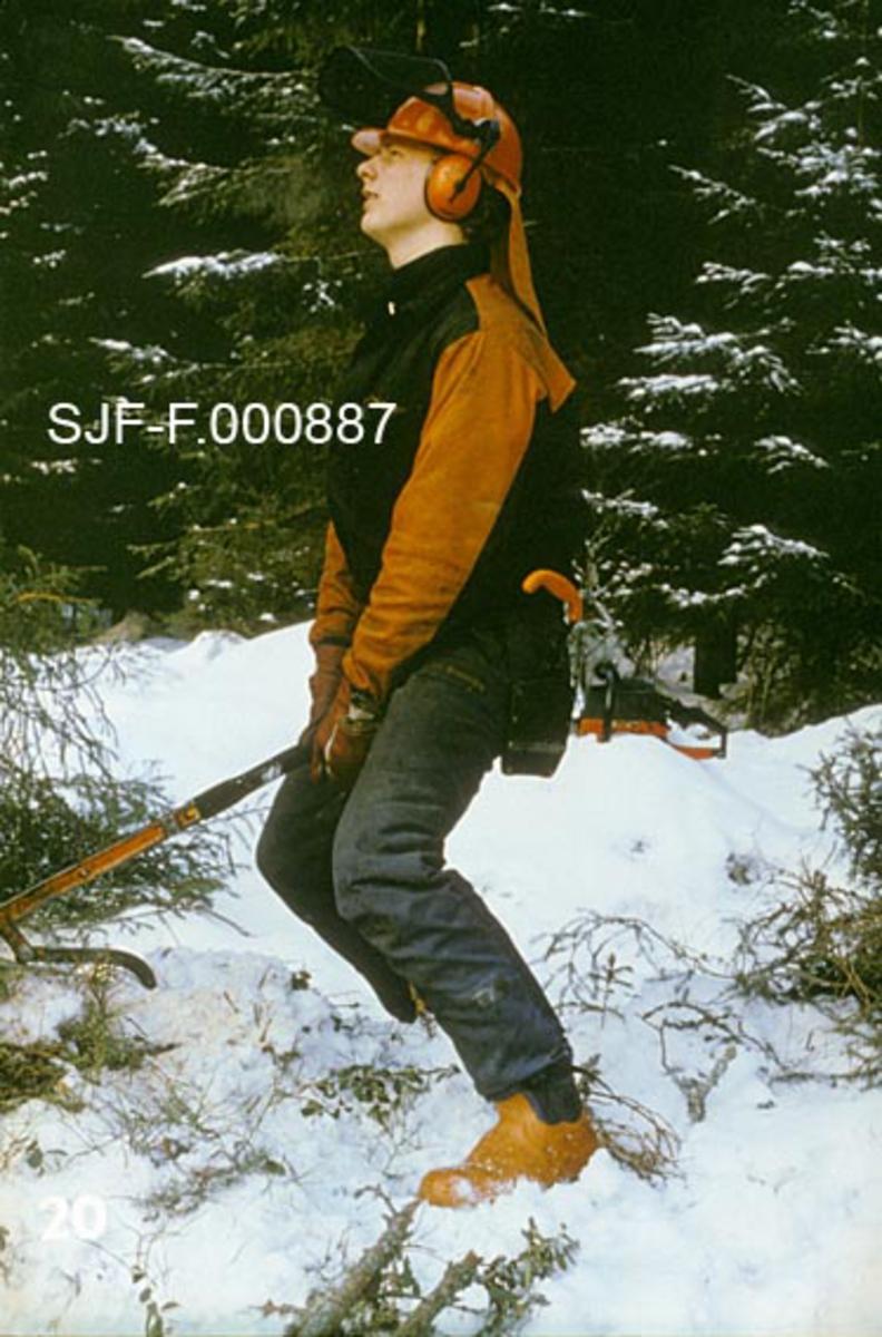 """Bruk av fellespett under skogsarbeid.  Fotografiet viser en skogsarbeider idet han drar et fellespett oppover, for å få det nesten avskårne treet (som befinner seg utenfor venstre bildekant) til å velte.  Mannen har oransje vernestøvler med ståltupp, mørkeblpå beavernylonbukser, svart jakke med oransje ermer og skulderparti.  På hodet har han en oransje hjelm med oppslått ansiktsvisir, øreklokker og nakkebeskytter (slør), som skal hindre at han får snø i halslinninga og blir vår og kald på ryggen.   Dette fotografiet inngikk i en undervisningsserie, som ble produsert og distribuert av Landbrukets Film- og Billedkontor i 1985.  Med serien fulgte det et teksthefte, der produsent Ronald Fredlund skrev følgende tekst knyttet til dette bildet:  """"Felling av treet (Bruk av fellespett).  Treet kan nå brytes over.  Stå med bred benstilling og med begge hendene på fellespettet.  Plasser kroppen så nær fellespettet som mulig og løft med rett rygg. """"   Denne teksten gir et godt innblikk i innsikter og holdninger som preget skogsarbeidet i norske fagmiljøer på 1980-tallet."""