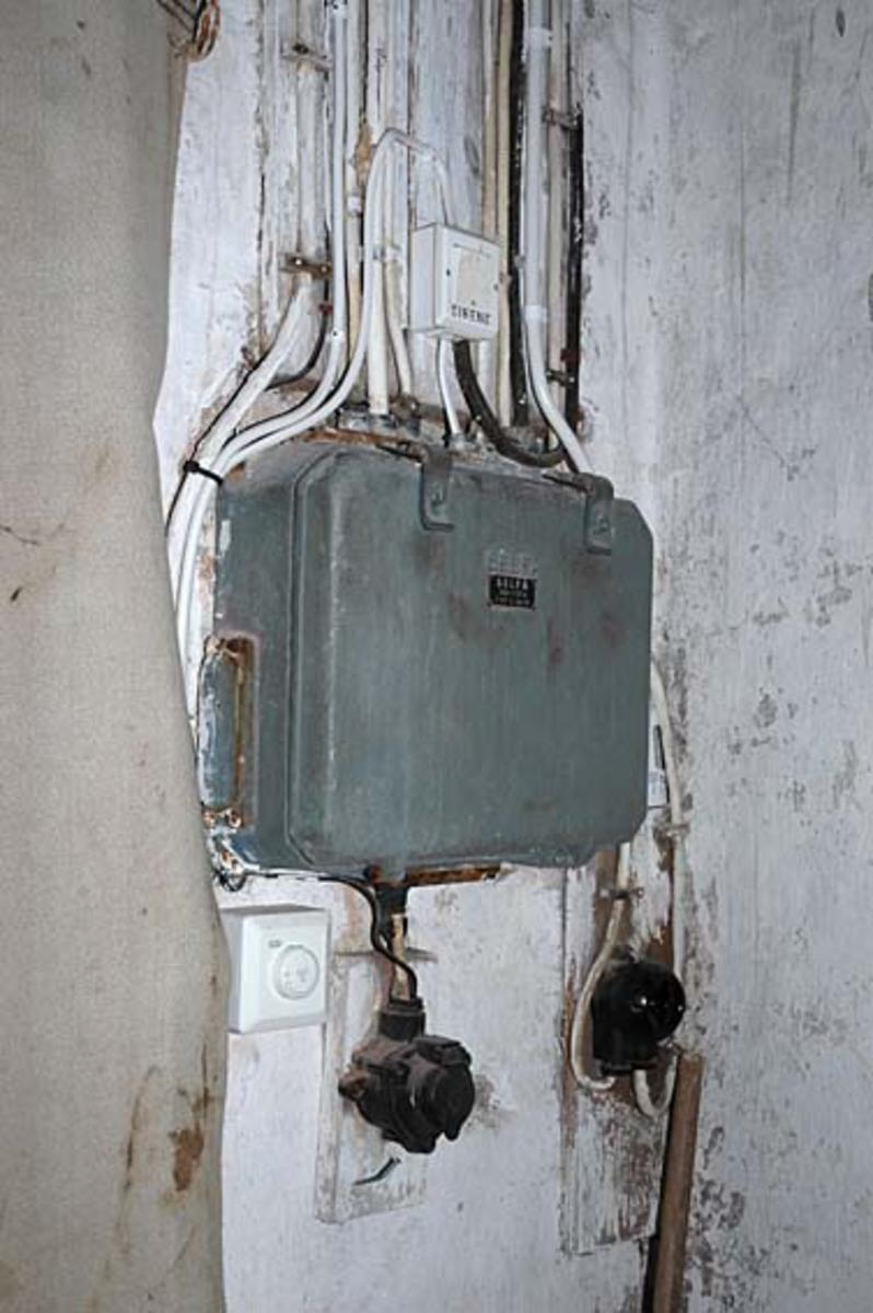"""Sikringsboks i Klevfos Cellulose- & Papirfabrik, som siden 1986 har vært drevet og vedlikeholdt som Klevfos industrimuseum. Denne sikringsboksen er plassert ved inngangen til hollenderisalen i fabrikken.  Bildet viser også hvordan det gamle elektriske anlegget i fabrikken er supplert med en del nyere elementer (ledninger og brytere).  Øverst er bryter til pausesignalet som ble kalt """"fabrikkfløyta"""" i Klevfos. Den ringte ut og inn for """"duggurd'n"""" og """"mædda`n"""", og ved vaktskifter når fabrikken gikk med treskift-ordning. Dette er et horn på taket, som høres over hele Ådalsbruk. Til høyre under er bryter for taklys. Løten."""