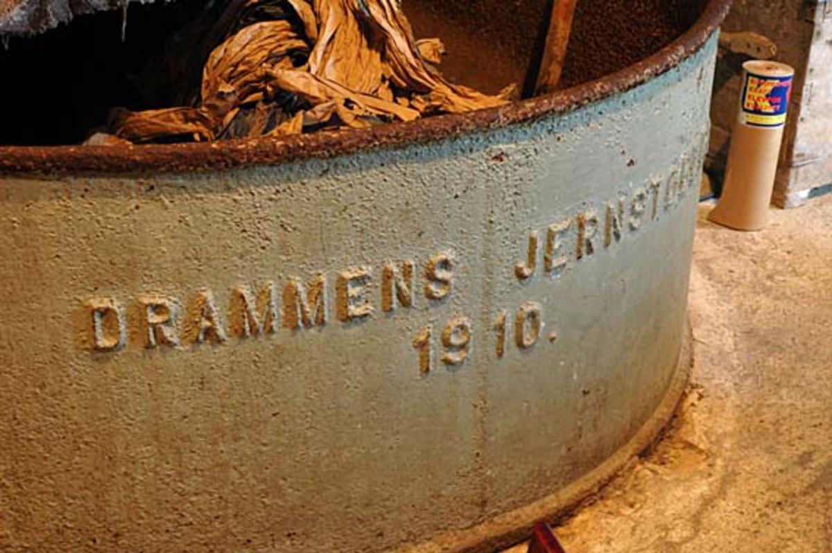 """Fra hollenderiet ved Klevfos Cellulose- & Papirfabrik i Løten.  Her ble råstoffene som skulle inngå i produksjonen blandet og malt.  Fotografiet viser fronten på hollenderkaret.  Dette er et digert støpejernstrau, der produsentens navn og produksjonsåret er innstøpt i opphøyet relieff:  """"DRAMMENS JERNSTØPERI 1910"""".  Dette forteller at denne maskinen ble innkjøpt og montert i forbindelse med at Klevfos-fabrikken i 1910-11 ble gjenoppbygd etter den store brannen som rammet anlegget i høsten 1909.  Hollenderen ble altså brukt til å blande og male papirmassen i.  Det dreier seg om et digert kar med en innvendig midtvegg, samt en valse (såkalt «kubbe») og et «grunnverk».  Ytterflatene på de roterende hollenderkubbene var besatt med skinner eller «kniver» av stål eller fosforbronse.  Disse maler mot det faststående grunnverket, som også har kniver av samme materiale.  Malingsgraden (fibrilldannelsen) hadde stor betydning for papirkvaliteten. Ådalsbruk."""