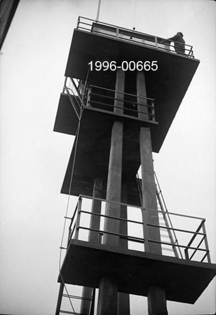 Tårnet på Rafjell skogbrannvakstasjon øst for innsjøen Nuguren i Brandval, Hedmark.  Tårnet ligger 585 meter over havet.  Det ble bygd 1934 med tilskudd fra forsikringsselskapet Skogbrand.  Eier var Brandval kommune, som seinere er sammenlått med Kongsvinger.   Tårnet er utført i armert betong og står på ei bergflate. Det har fire loddrette bein eller pillarer som gir tårnet et rektangulært grunnplan, der det etter fotografiet å dømme inngår et rektangulært rom med inngang i den ene kortenden.  Adkomsten til utkikksstedet på toppen skjer via jernstiger og to plattformer med jernrekkverk, den nedre er støpt rundt to av pillarene, den øvre rundt alle fire.  På toppen står ei rektangulær utkikkshytte på en noe utkraget plattform med jernrekkverk.  Fotografiet er tatt fra en posisjon tett inntil tårnfoten oppover mot utkikkshytta.  Der står en mann ved rekkverket foran hytta.