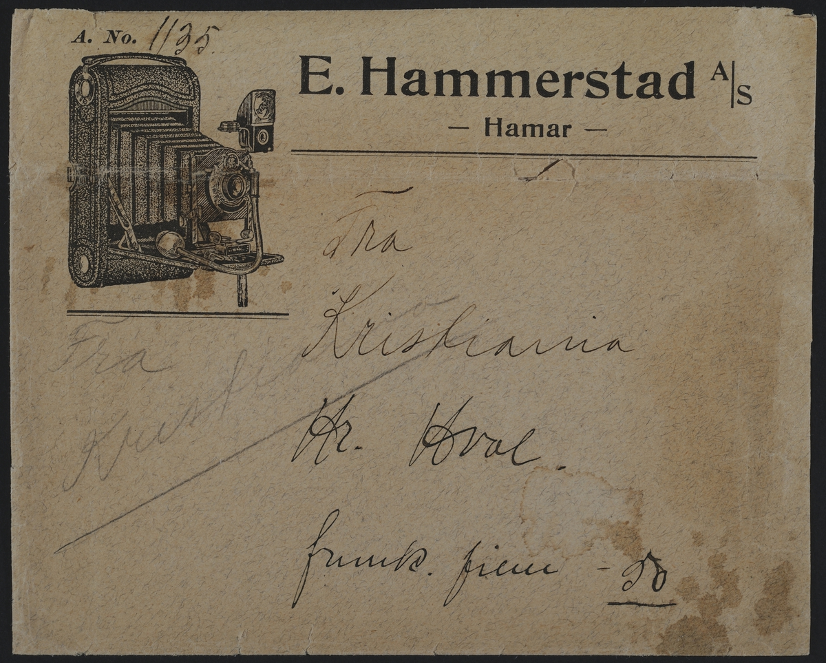 """Fotokonvolutt. E. Hammerstad A/S Hamar.  E. Hammerstad -optiske artikler, sykepleierartikler-fotografiske artikler - og parfymeri.  """"E. Hammerstad startet sin forretning som optisk instrumentmaker og metallstøper i 1862 og fra 1868 var han også bandagist og fra 1877 justermester. Han drev sin forretning til den i oktober 1910 ble overtatt av urmaker A. M. Sveen og gullsmed P. Børke, og ved Sveens død gikk overrettsakfører Hjelmstad inn som medeier. I. juni 1918 ble forretningen overtatt av et aksjeselskap bestående av Trygve S. Hansen. Moriitz Hansen og S. Christiansen, med den første som disponent. Fra november 1928 driver Trygve S. Hansen forretningen som eneinnhaver. Hansen var utdannet som gullsmed, men etter at han hadde arbeidet som sådann en tid i Amerika, skaffet han seg seg spesiallutdannelse som optiker ved optikerkurser i Tyskland. Etthvert ble forretningen utvidet til å omfatte fotografiske artikler med kopieringsantalt og parfymeri. """" Sitat fra """"Hamars næringsliv i jubileumsåret 1949"""""""
