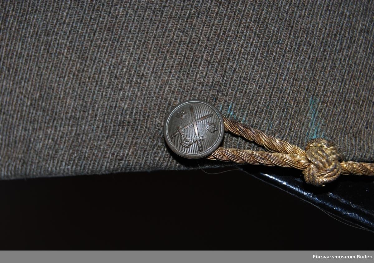 Gråbrungrönt ylletyg. Framtill nationalitetsmärke m/1941 och nedanför detta bronsfärgat mössmärke m/1939 med blå emalj för officerare. Mössrem i form av bronsfärgad snodd för kompaniofficerare, fäst vid mössans sidor med intendenturkårens knapp modell mindre.