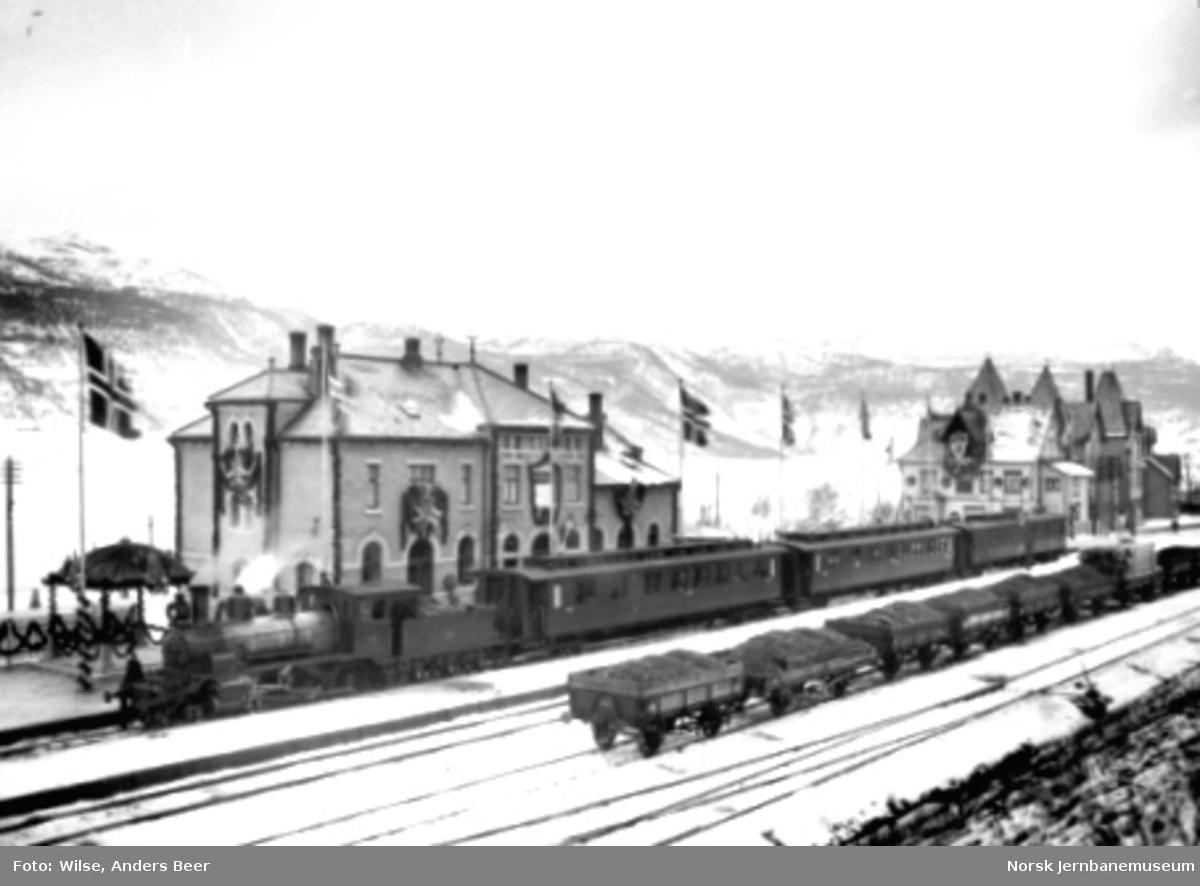En pyntet Voss stasjon med persontog østover ved Bergensbanens åpning