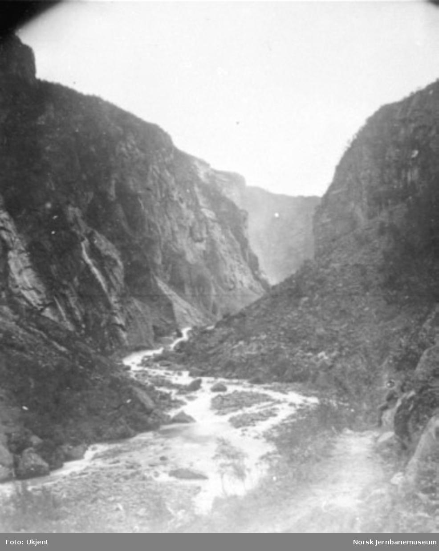 Ukjent elvedal med en veg langs elvebredden