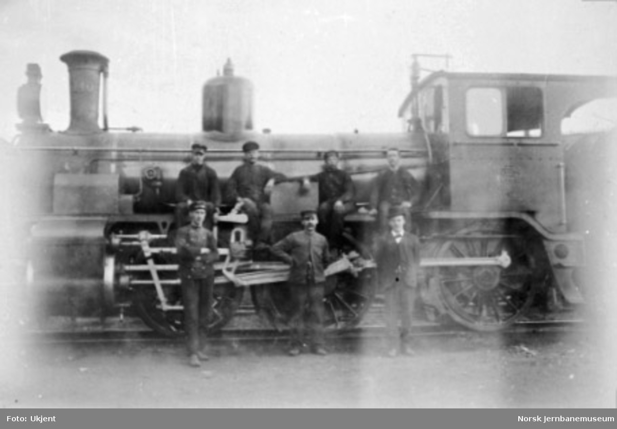 Sju mann poserer foran damplokomotiv type 15c nr. 140
