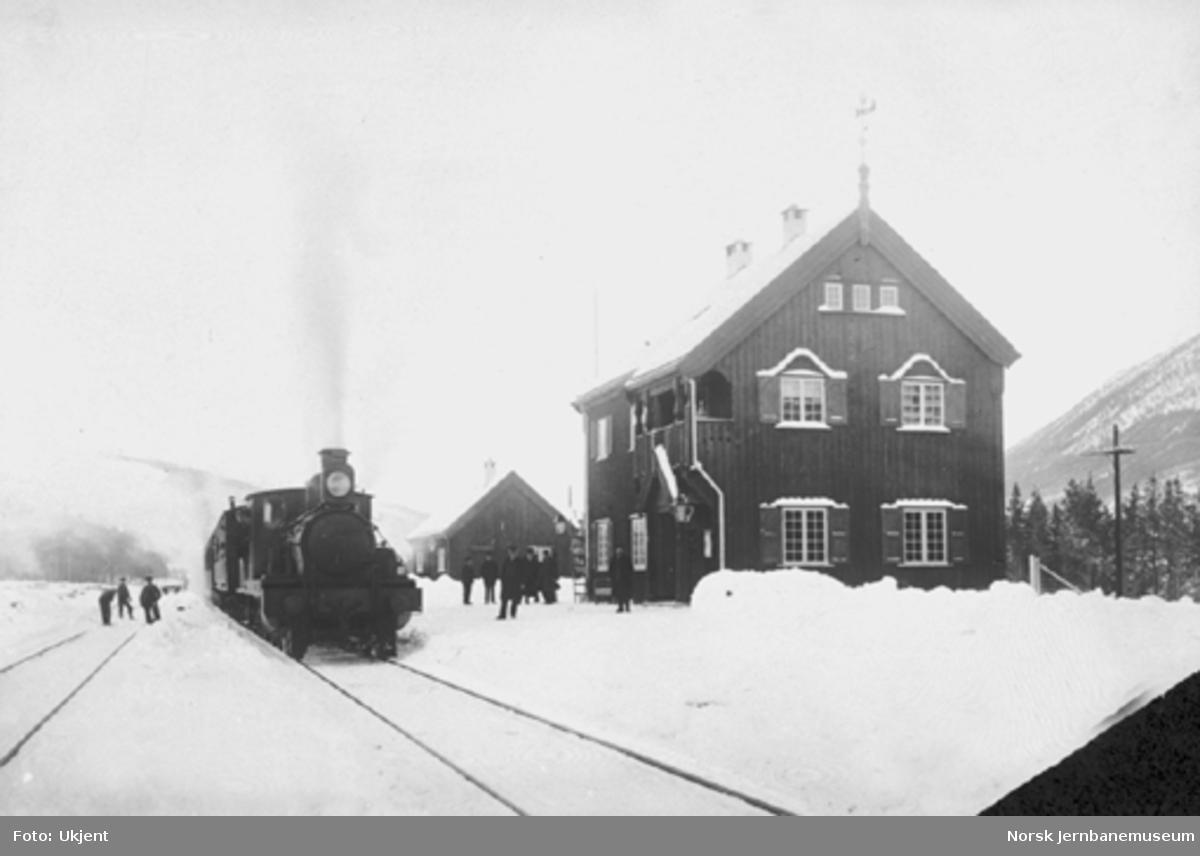Vinterbilde fra Brennhaug stasjon med stasjonspersonalet på plattformen og et damplokomotiv av type 11 med persontog i spor 1