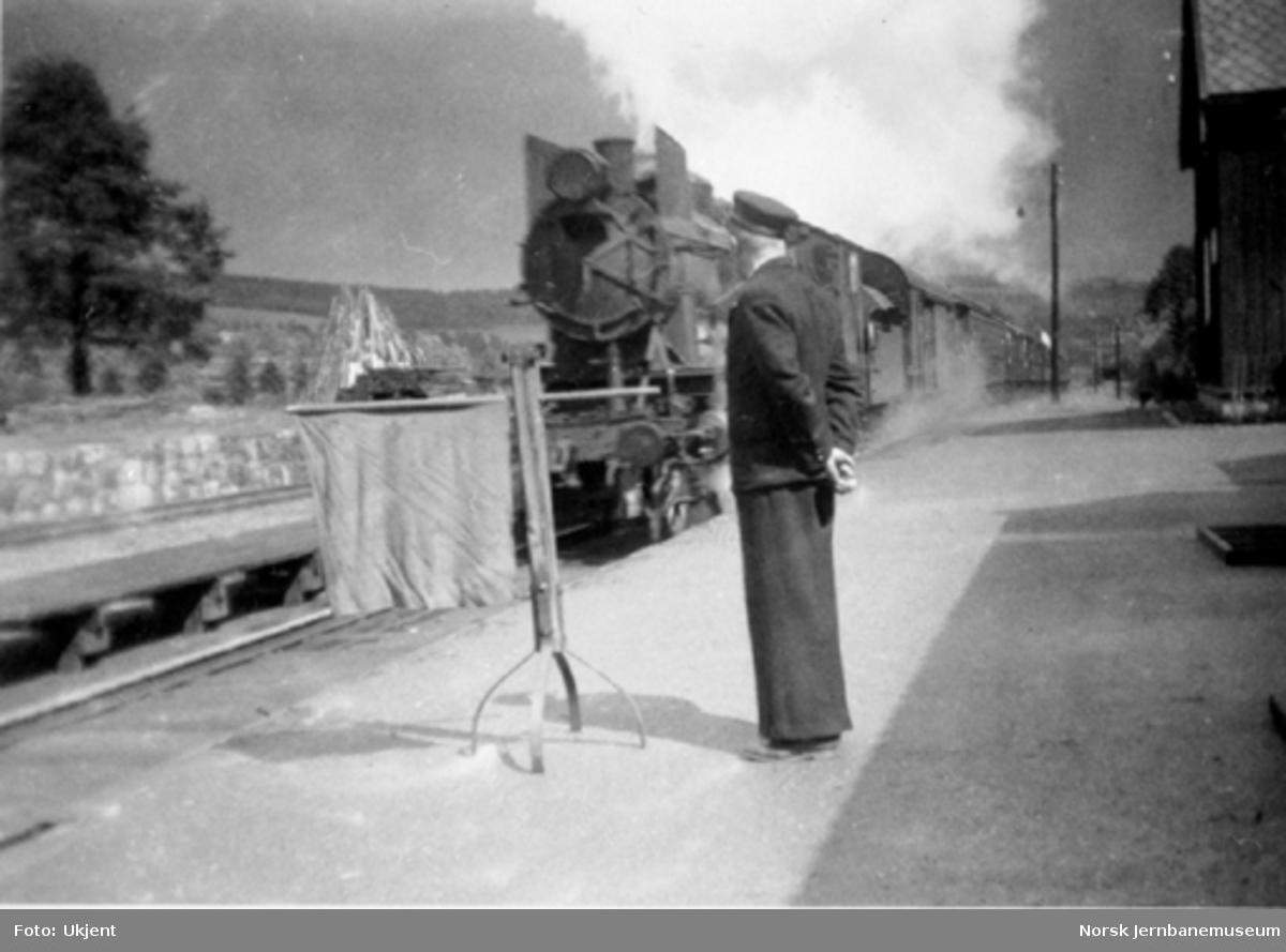 Stasjonsmester med grønt flagg og ankommende tog, muligens Hunder stasjon