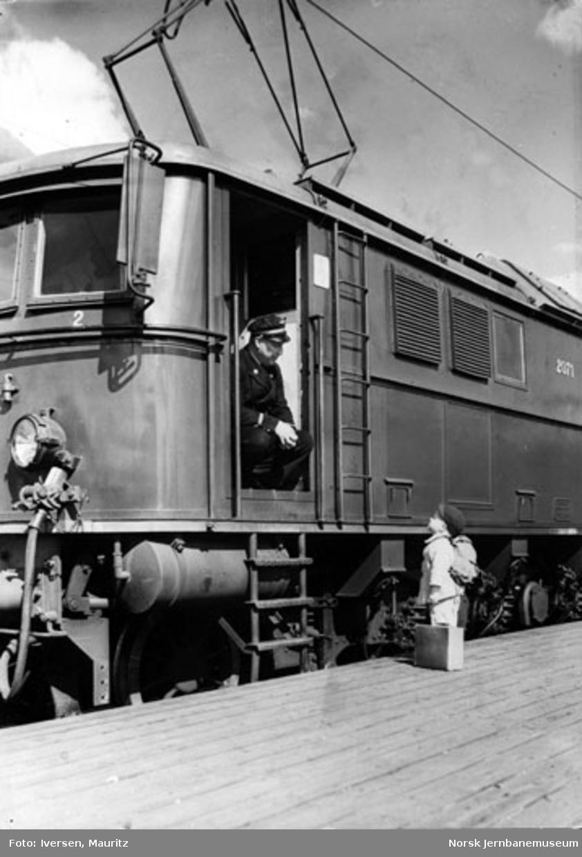 En liten gutt med koffert og ryggsekk snakker med lokomotivføreren på elektrisk lokomotiv El 8.2071