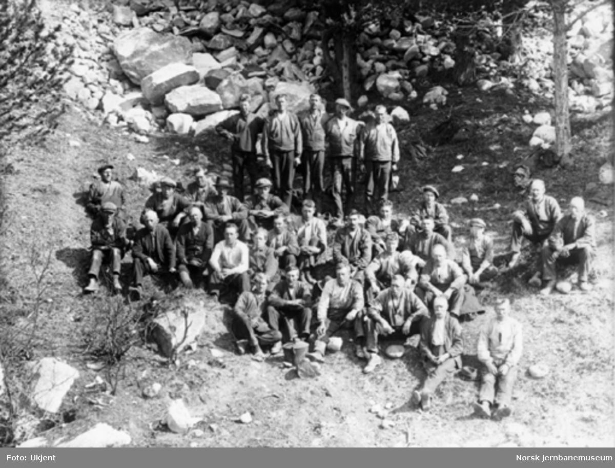Gruppebilde av 30-40 anleggsarbeidere sittende og stående i en skråning