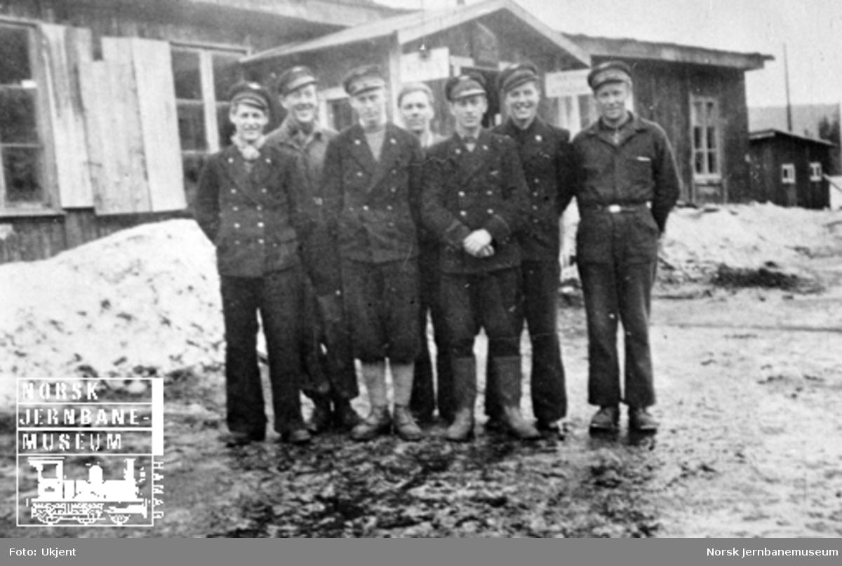 Gruppebilde av sju jernbaneansatte, de fleste uniformerte, på plattformen på Grønfjelldal stasjon våren 1945
