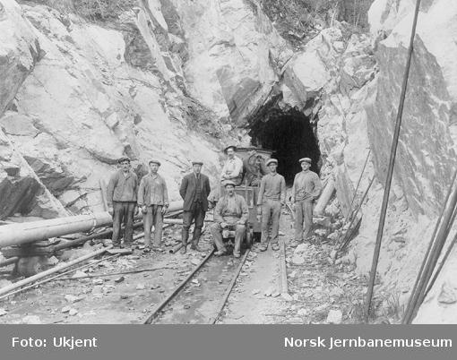 Arbeidslaget utenfor Vadfoss tunnel med et motorlokomotiv i bakgrunnen