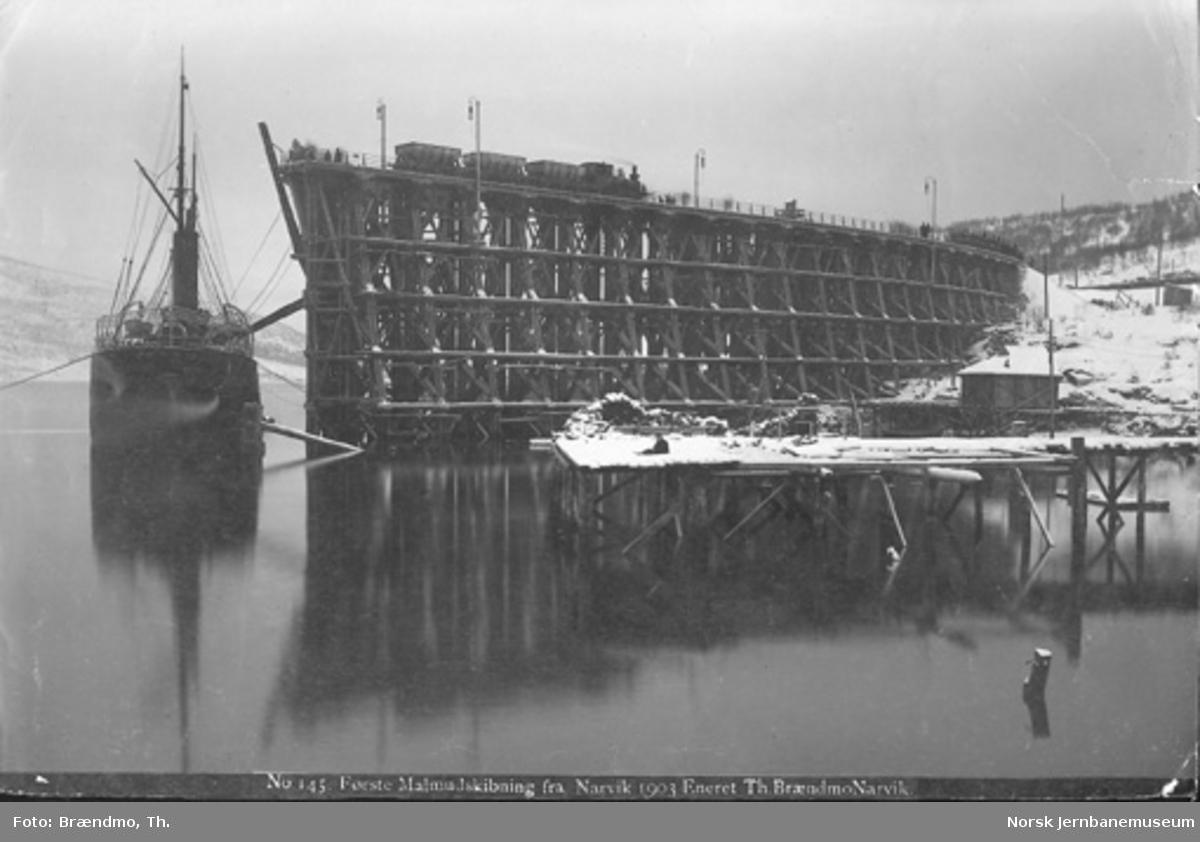 Første malmutskipning fra Narvik; damplokomotiv med malmvogner på kaien og dampskip som lastes