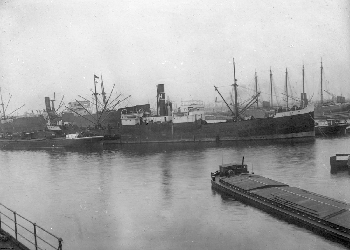 """Dampskipet D/S """"Aslaug"""" ankret opp, med flere skip i bakgrunnen, og ett i forgrunnen."""