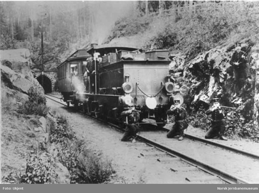 Svensk vakthold fra Värmlands regiment ved vestre enden av Brunnbergstunnelen, tre soldater oppstilt foran et damplokomotiv og en personvogn