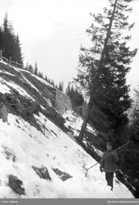 Veganlegget Madsveen - Årnes ved Losnavatnet : utrast parti av vegmuren med baneformannen som markerer restene av den nedfalne vegmuren