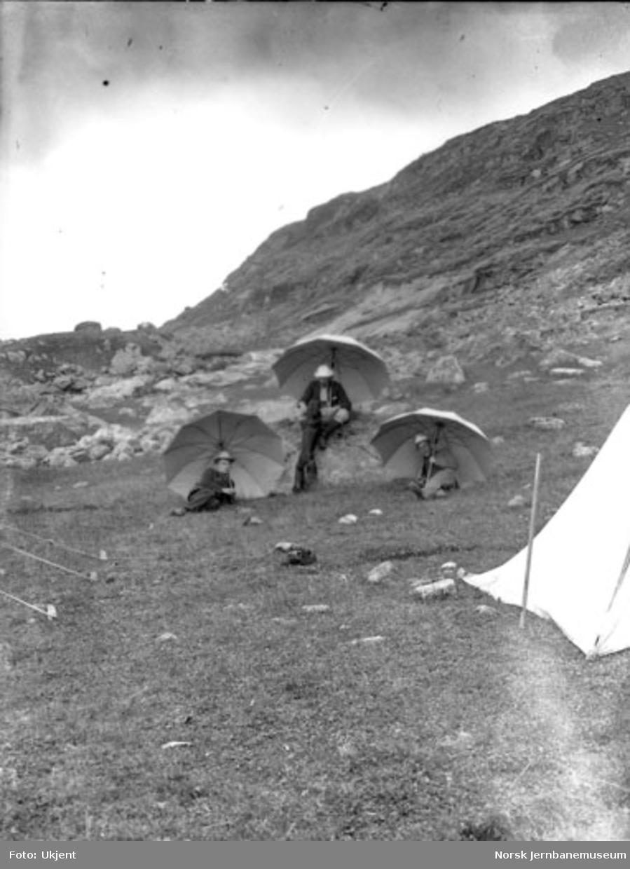 Tre menn ved en teltleir for stikningspersonalet