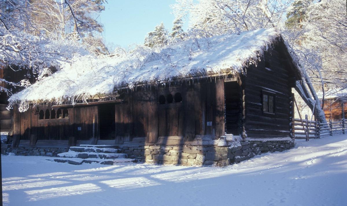 """STUE FRA KJELLEBERG I VALLE, CA. 1650-1700 Overført til museet 1912, gjenoppført 1913   Huset består av to stuer, """"gamlestog"""", årestua, og """"nyestog""""– stua med peis og vinduer. Da årestua ble bygd i 1650-årene hadde den tre rom: stue, forstue og kove. Huset ble utvidet med """"nyestog"""" tidlig på 1700-tallet. Der årestuas forstue og kove hadde vært ble det nå en gang mellom stuene, med trapp opp til et loft over """"nyestog"""". Loftet avløste fjøstrevet som soveplass for ungdommen.  (Tekst hentet fra By og bygd 43, 2010)"""