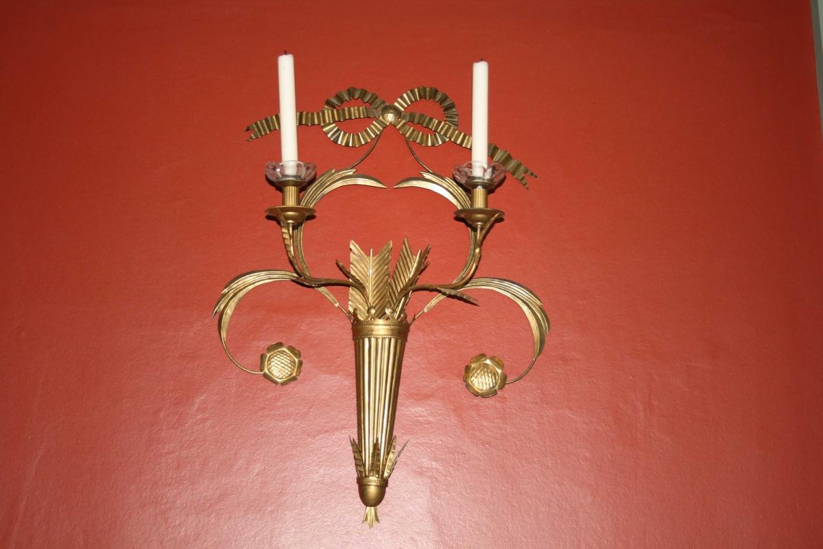 Formet som pilekogger med to lysholdere, forgyldte. Laget til 150-års jubileet 1964. Kopiert av gjørtler C. P. larsen, Oslo etter originale tilhørt Carsten Anker.
