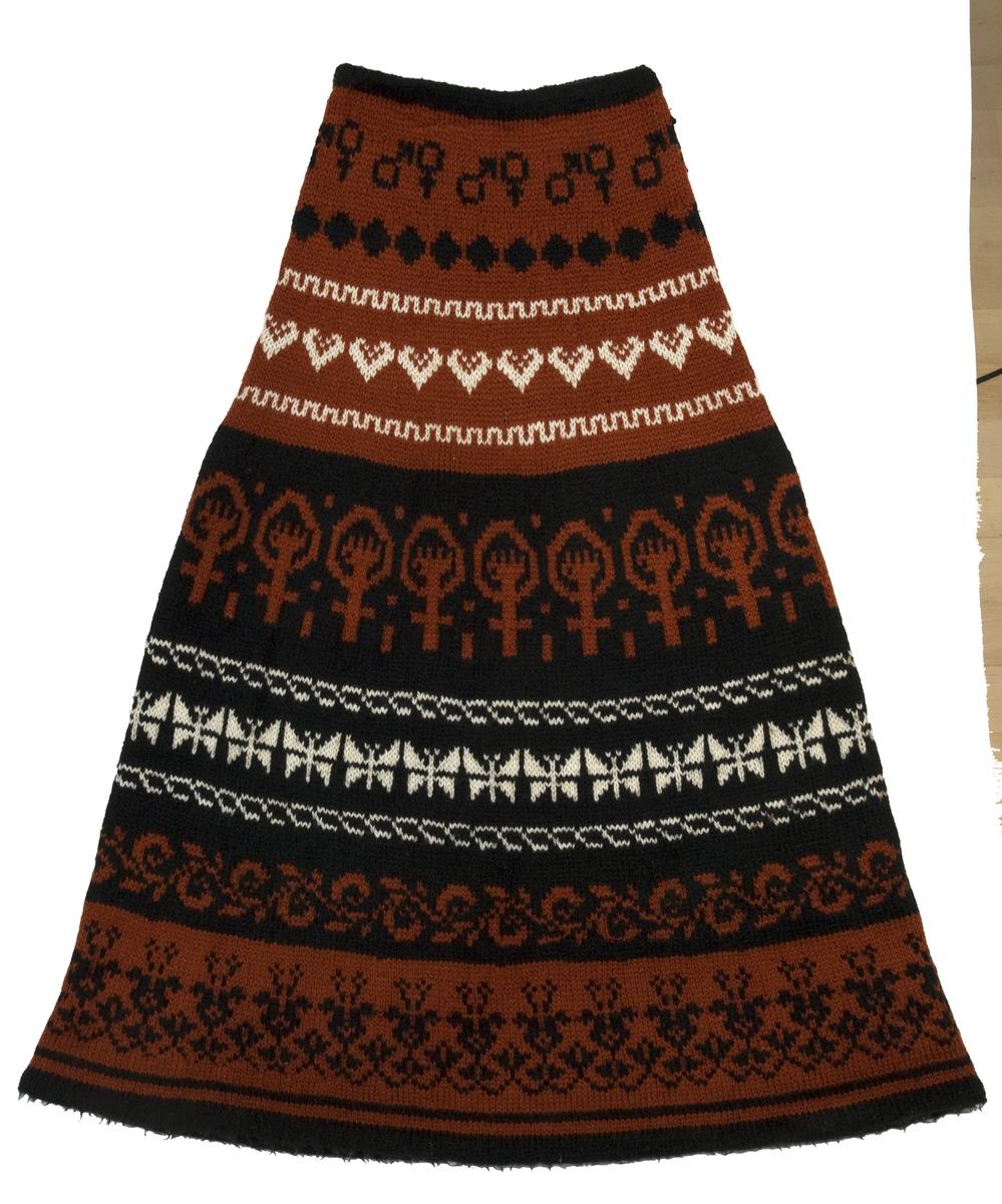 Langt fotsid strikkeskjørt med motiver i svart, hvitt og rødt med småmønstrete horisontale border på hele lengden.